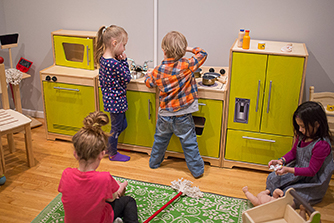 Four kids playing in a toy kitchen